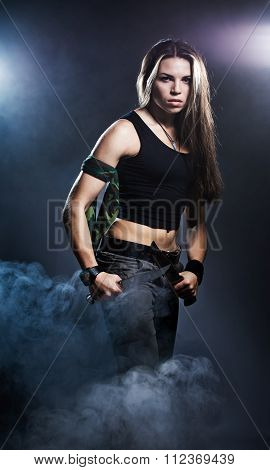 Sexy woman holding daggers with smoke studio shot