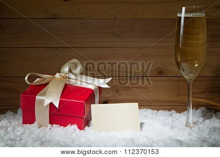 Concept Of Celebration With Gift Box, Empty Card, Champagne Glass On Snow And Wooden Background.