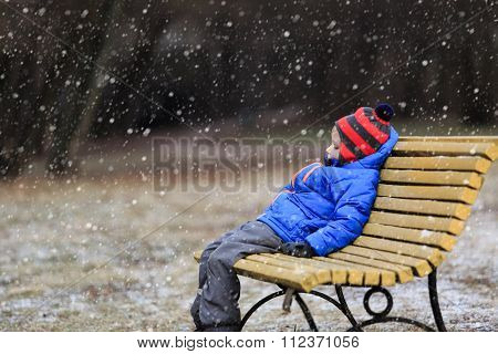 little boy sitiing on bench in winter