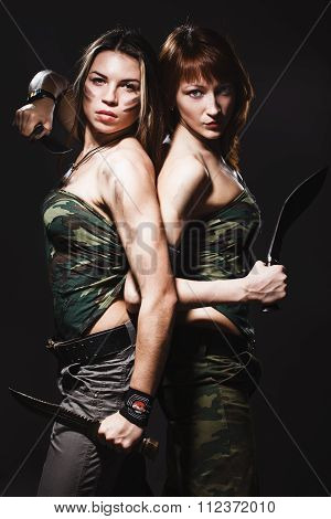 two sexy women with gun and dagger on gray