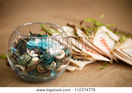 Aroma Mix Of Dry Flowers, Herbs, And Berries Inside A Transparent Glass Vase And Small Sachet Bags