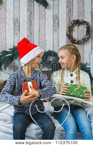Happy children sitting on bed and holding gifts. Waiting for Christmas. Celebration. New Year.