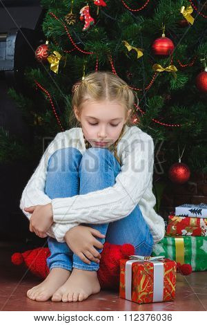 Pensive sad girl sits near a gifts and waiting New Year or Christmas