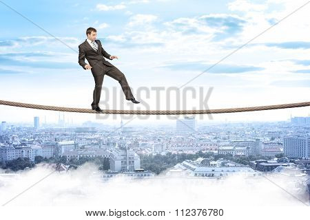 Businessman gently walking on rope
