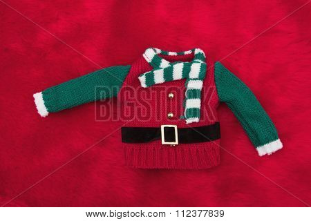 Green And Red Elf Christmas Sweater On Red Plush Fur
