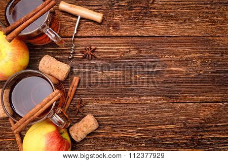 Cider and apples on a wooden table.