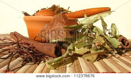 Licorice root placed in a clay pot with wooden spoon.