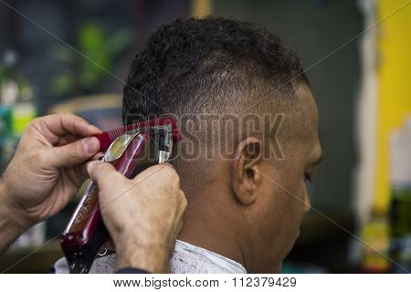 Barber trims hair of client, close up.