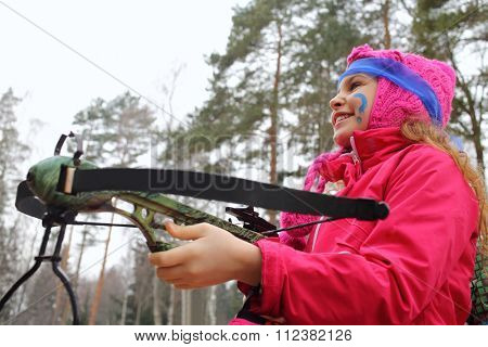Girl with blue paint on his face and crossbow in her hands in forest