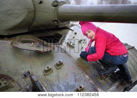 Girl in a pink jacket and hat climbed on the Soviet tank