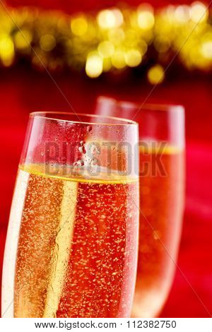 closeup of a pair of flute glasses with champagne against a red background ornamented with a golden tinsel