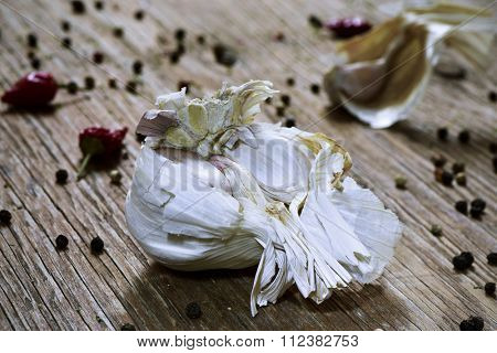 closeup of a head of garlic and some garlic cloves on a rustic wooden table