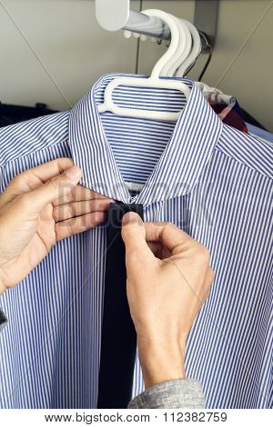 closeup of a young caucasian man choosing a tie and a shirt from the closet