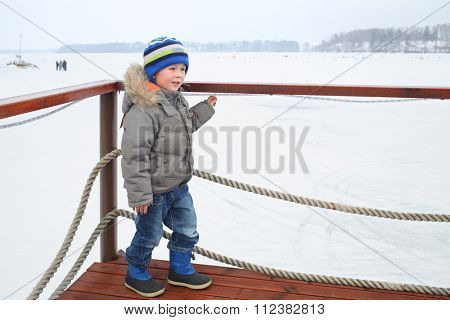 Little boy in a winter jacket and hat standing on the berth near the snow-covered pond