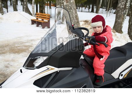 Little girl in red overalls sitting behind the wheel of a snowmobile in forest