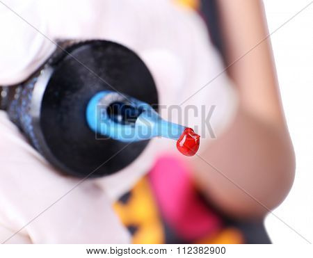 Close up view on tattoo machine with red paint in hand against unfocused background