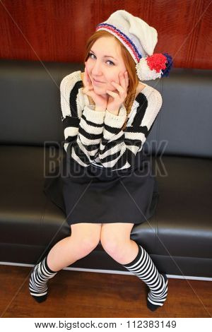 Girl with braces in a white hat with a pompom and a striped sweater and socks sits on a chair