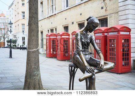 LONDON, UK - DECEMBER 20: Young Dancer statue, by Enzo Plazzotta, with line of red phone booths in the background. December 20, 2015 in London.