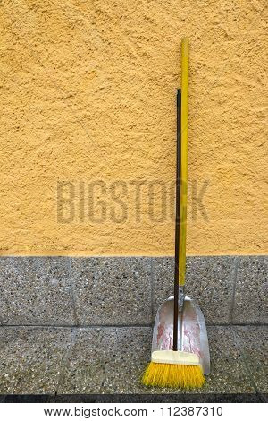 An old styled yellow broom and metal dustpan leaning on yellow wall