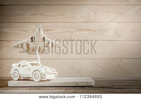 Wooden Toy Plane Hand Carved Model And A Car On Wood Background , Selective Focus.