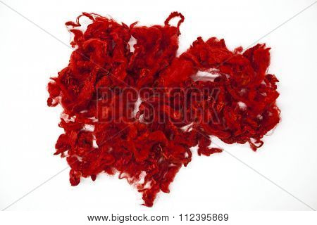 Red piece of Australian sheep wool Merinos breed close-up on a white background.