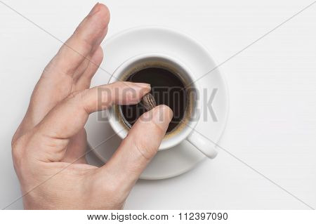 Male Hand Holding Coffee Bean Over Cup Of Black Coffee Against White Background Top View With Space