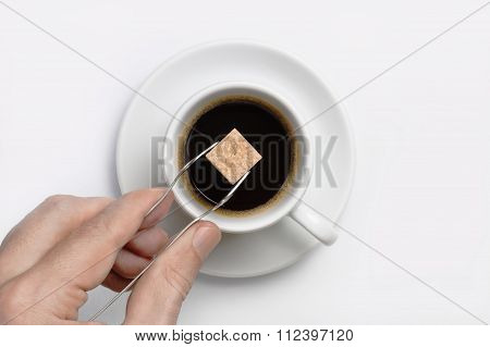 Male Hand Holding Sugar Tongs With Cane Sugar Cube Over Cup Of Black Coffee Against White Background