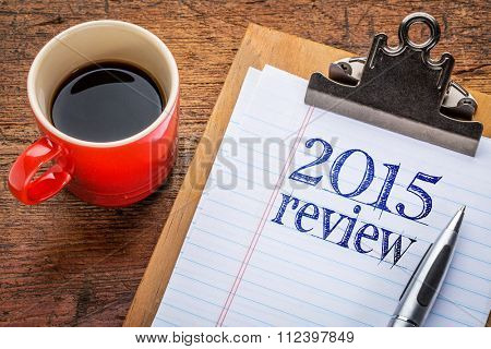2015 review on clipboard and coffee against grunge wood desk