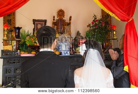 A wedding with bridal and groom of a just married couple wishing for happiness in front of altar