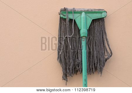 A Mop Lying Against A Wall.