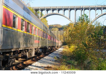 Passenger Train Under Arched Bridge