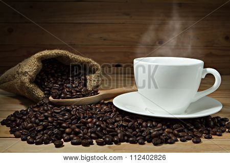 Coffee Cup And Coffee Beans On Wooden Background.