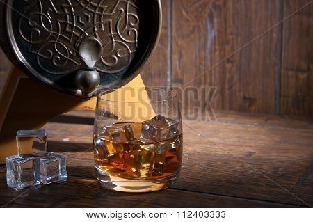 Glass Of Whiskey  With Ice  Beside A Barrel On Wooden Backgroun