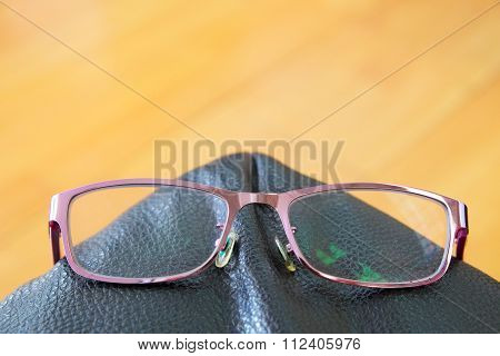 Violet eye glasses with green reflection on a lens at the border of black leather seat.