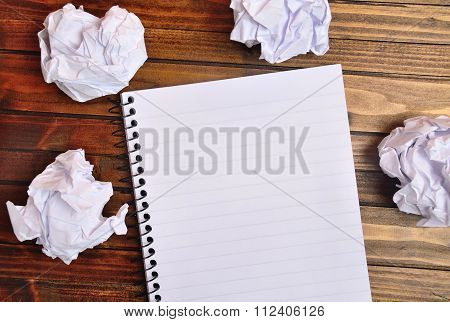 Notebook with crinkled paper on wooden table
