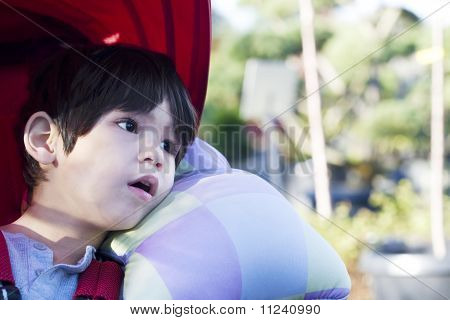 four year old boy looking quietly off to side