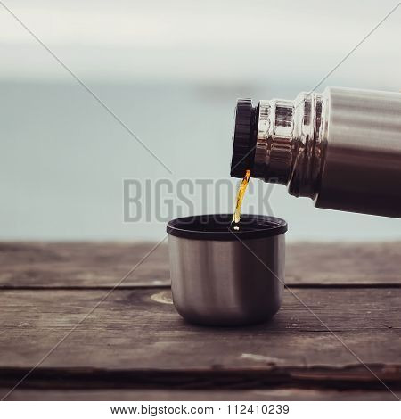 Pouring Tea From Thermos Outdoor