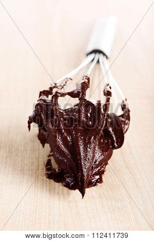 Corolla with chocolate cream on wooden background