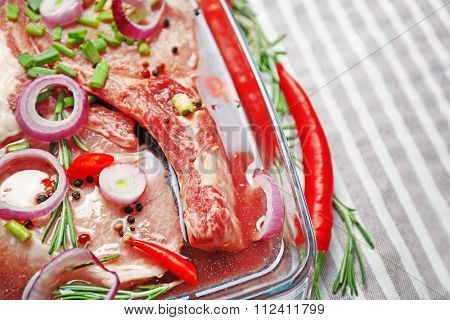 Marinating meat with spices on table, close up