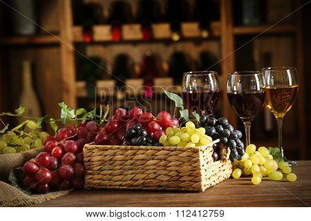 Grape in wicker box on a table on wine bottles background