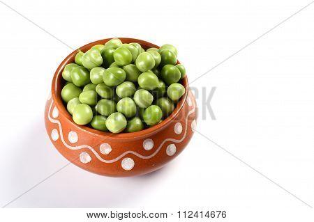 Fresh Green Peas in clay pot
