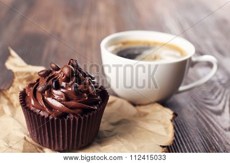 Chocolate cupcakes and coffee on craft paper
