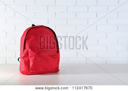 School backpack on wooden table, on wall background