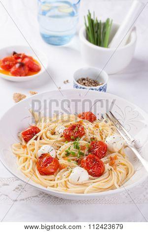 Italian spaghetti pasta with baked cherry tomatoes mozzarella and spring onions