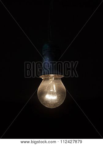 Old Dusty Light Bulb Glowing In The Dark