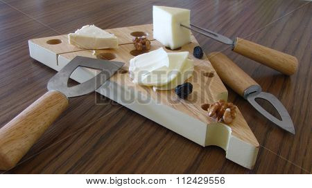 Cheeses sliced with wood handle cheese knife on bamboo board.