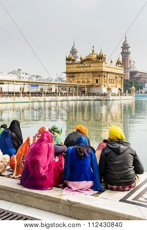 Sikh Pilgrims Sitting At The Lake of the Golden Temple In Amritsar.
