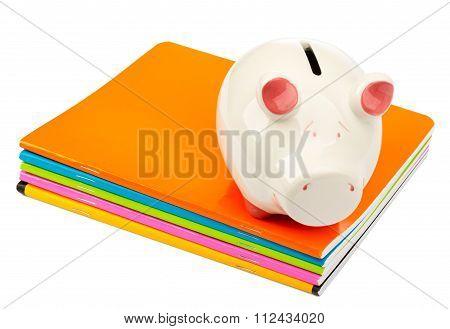 Piggy bank on pile of copybooks