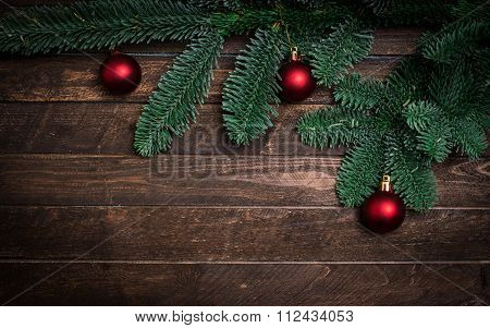 Christmas New Year Decoration Composition. Top View Of Fur-tree Branches And Balls Frame On Wooden B