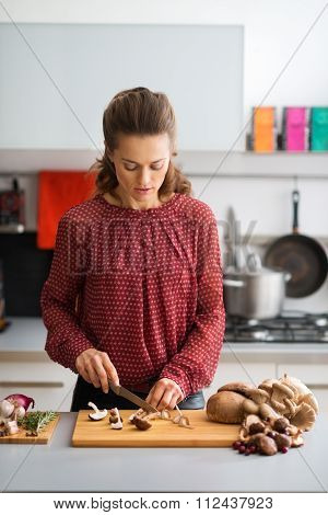 Woman In Kitchen Looking Down While Cutting Mushrooms